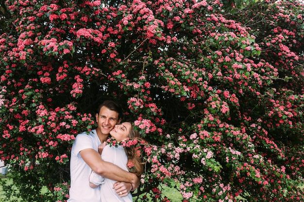 Jovem casal feliz apaixonado ao ar livre. amar o homem e a mulher em uma caminhada em um parque florido de primavera