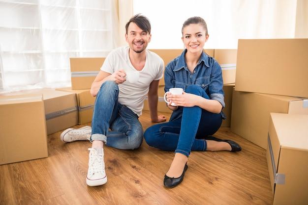 Jovem casal feliz bebendo chá e café.