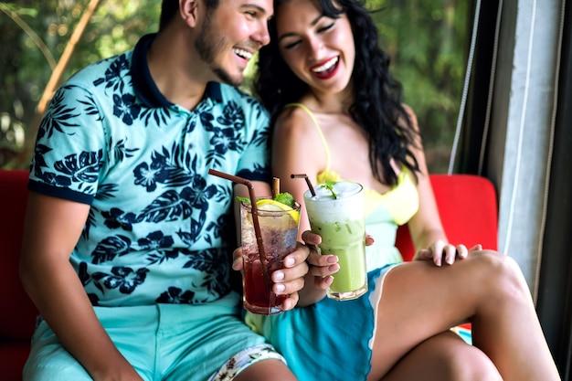 Jovem casal feliz bebendo saborosos coquetéis doces em bar tropical, sorrindo e se divertindo, roupas brilhantes e emoções positivas.