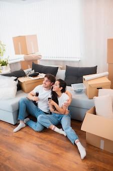Jovem casal feliz bebendo vinho, comemorando a mudança para a nova casa e sentado entre caixas. foto vertical