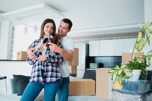 Jovem casal feliz bebendo vinho, comemorando a mudança para nova casa entre caixas.
