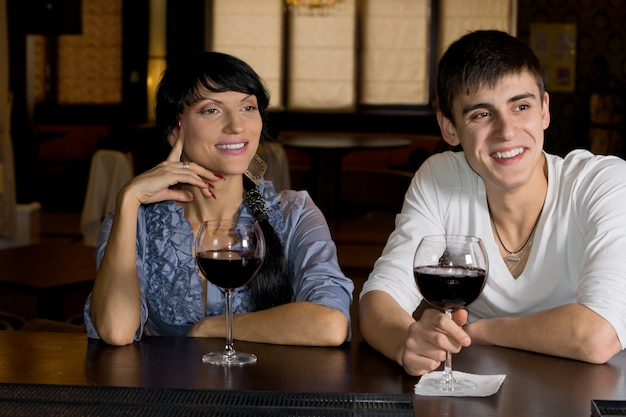 Jovem casal feliz bebendo vinho tinto no bar, sorrindo, divertindo-se