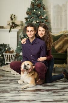 Jovem casal feliz carinhos com um cachorro sentado no chão perto da árvore de natal.