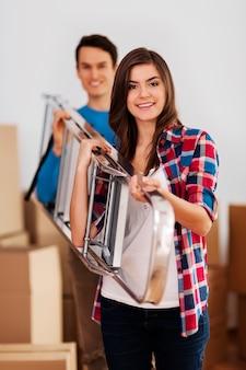 Jovem casal feliz carregando uma escada