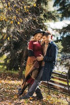 Jovem casal feliz, caucasiano, posando ao ar livre no dia de outono, uma jovem grávida abraça seu homem e ...