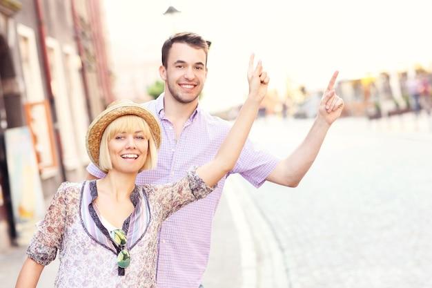 Jovem casal feliz chamando um táxi em uma cidade