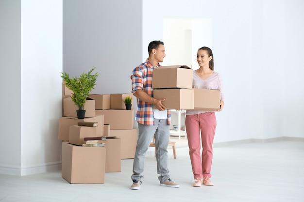 Jovem casal feliz com a mudança de caixas em seu novo apartamento