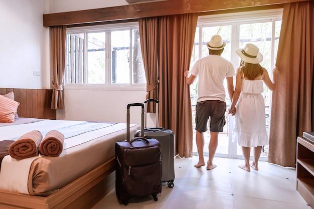 Jovem casal feliz com bagagem no quarto de hotel