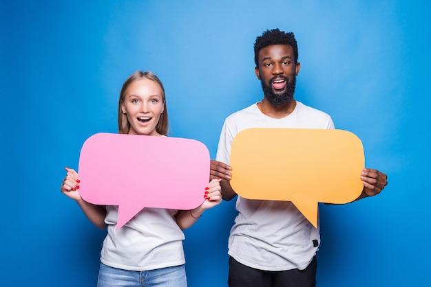 Jovem casal feliz com balões de fala de papel na parede azul