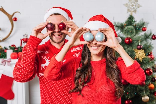 Jovem casal feliz com bolas ornamentais