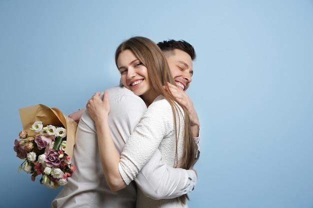 Jovem casal feliz com buquê de flores na luz