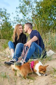 Jovem casal feliz com cachorro corgi sentado na areia