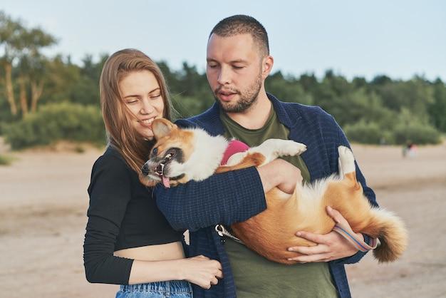 Jovem casal feliz com cachorro em pé na praia. vida familiar, união, marido e mulher relaxam juntos