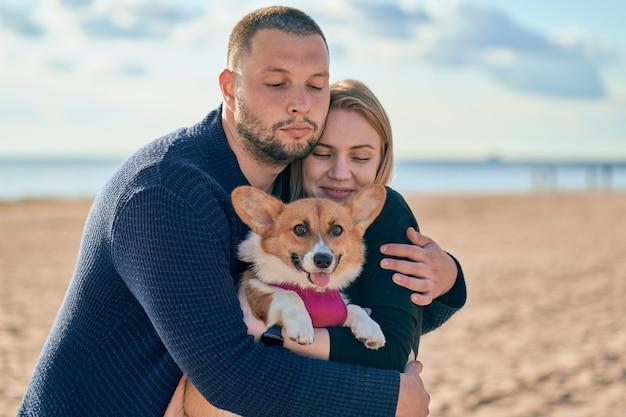 Jovem casal feliz com cachorro em pé na praia.