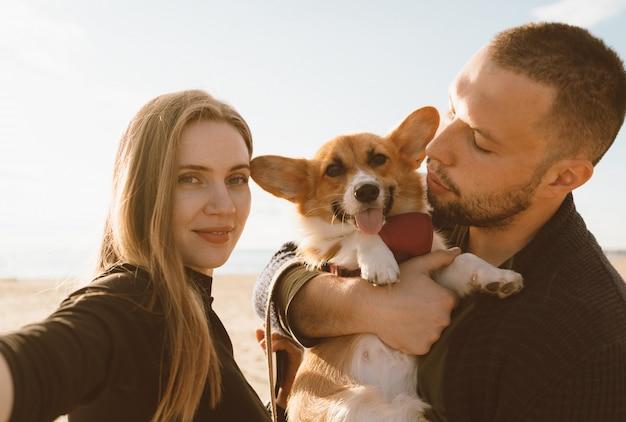 Jovem casal feliz com cachorro toma selfie na praia. linda garota, cara e cachorrinho corgi