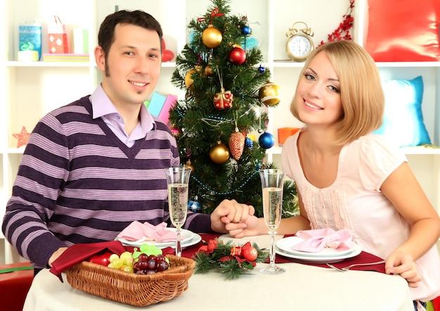 Jovem casal feliz com champanhe na mesa perto da árvore de natal