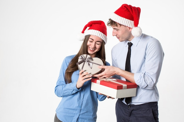 Jovem casal feliz com chapéu de papai noel e caixas de presente