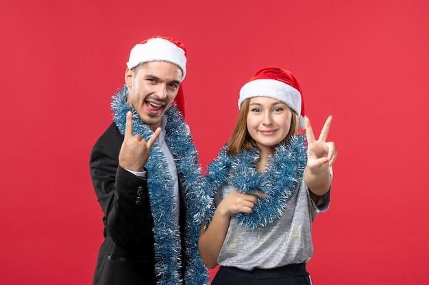 Jovem casal feliz com clima de ano novo na parede vermelha de frente