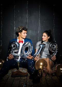 Jovem casal feliz com números de balões