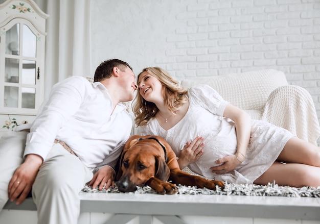 Jovem casal feliz com seu animal de estimação sentado no chão de seu novo apartamento