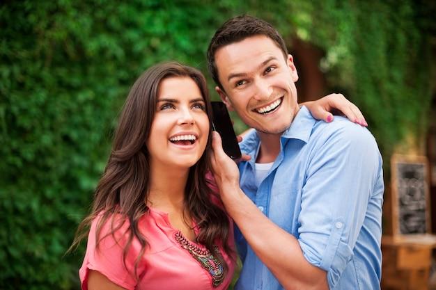 Jovem casal feliz com telefone inteligente
