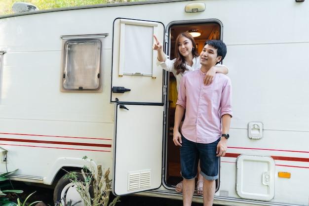 Jovem casal feliz com um trailer trailer van motorhome