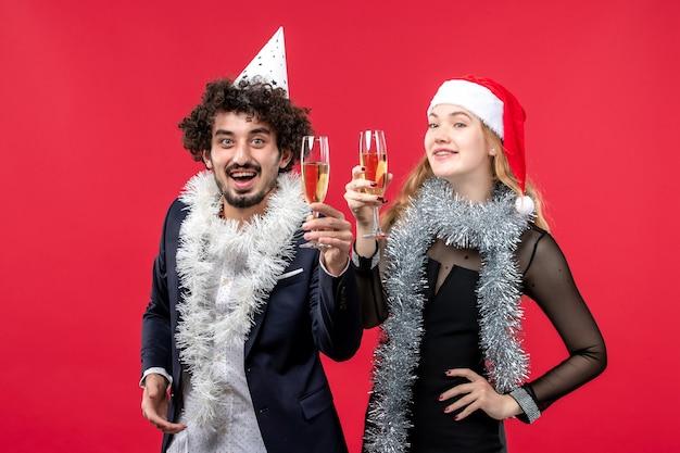 Jovem casal feliz comemorando ano novo na parede vermelha foto de amor de natal