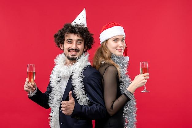 Jovem casal feliz comemorando o ano novo com a cor do natal