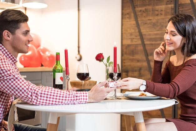 Jovem casal feliz comemorando o dia dos namorados com um jantar em casa bebendo vinho, felicidades.