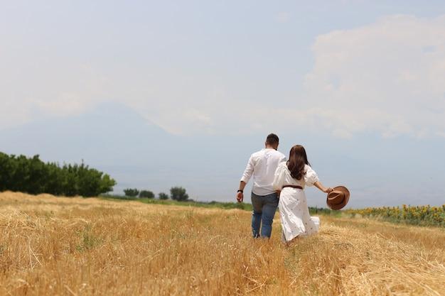 Jovem casal feliz correndo em um campo de grama seca com céu azul