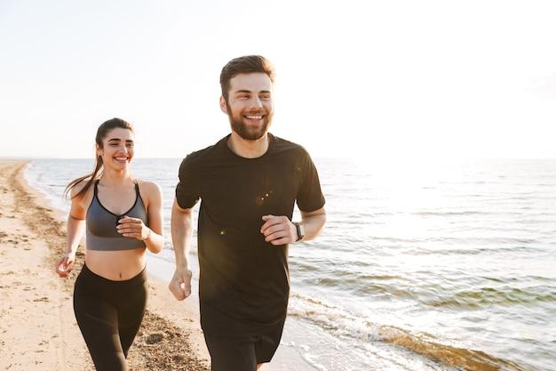 Jovem casal feliz correndo juntos na praia