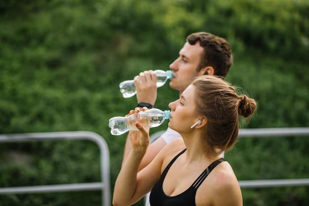 Jovem casal feliz correndo no parque da cidade com uma garrafa de plástico de água nas mãos, esportes conjuntos, alegria, estilo de vida saudável do esporte da cidade, fitness juntos, corredores, água potável, sede