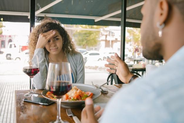 Jovem casal feliz curtindo juntos tendo um encontro em um restaurante.