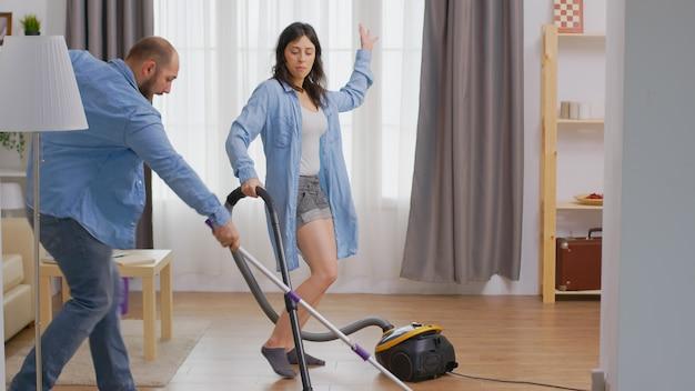 Jovem casal feliz dançando e limpando a casa usando aspirador e esfregão