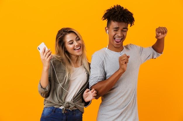 Jovem casal feliz dançando isolado na parede amarela ouvindo música com fones de ouvido