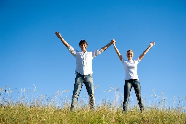 Jovem casal feliz dançando juntos em um prado de verão com as mãos ao alto