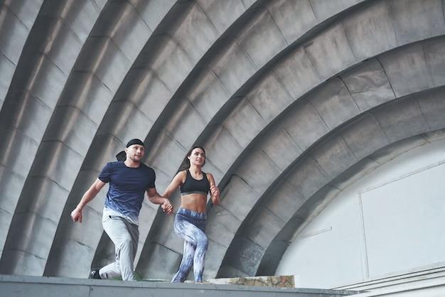 Jovem casal feliz de esportes na rua da cidade, realizando o parkour.