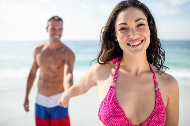 Jovem casal feliz de mãos dadas na praia