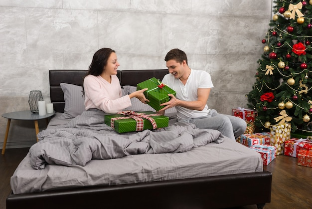 Jovem casal feliz de pijama dando presentes um ao outro enquanto está sentado na cama no quarto em estilo loft na manhã de natal