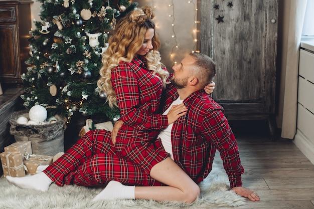 Jovem casal feliz de pijama sentado no chão com uma árvore de natal ao fundo