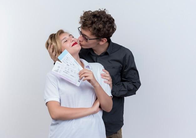 Jovem casal feliz de turistas, homem e mulher com passagens aéreas, se divertindo juntos, homem beijando sua namorada em pé sobre uma parede branca