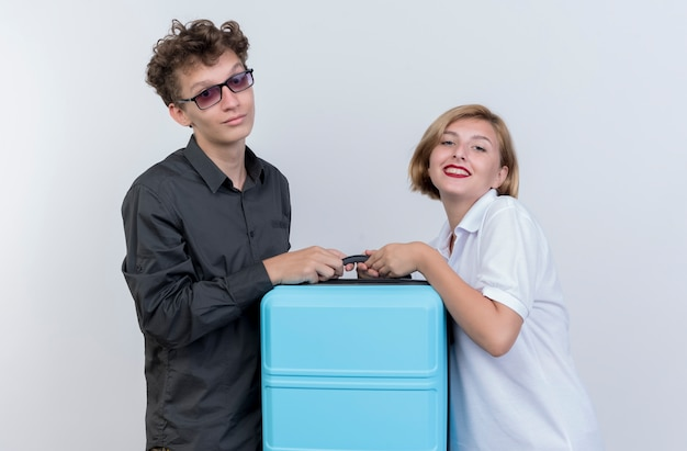 Jovem casal feliz de turistas, homem e mulher segurando uma mala, sorrindo sobre uma parede branca