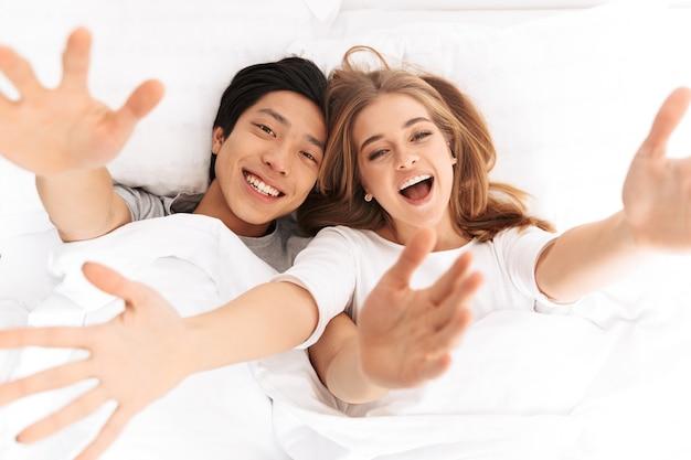 Jovem casal feliz deitado na cama com as mãos estendidas