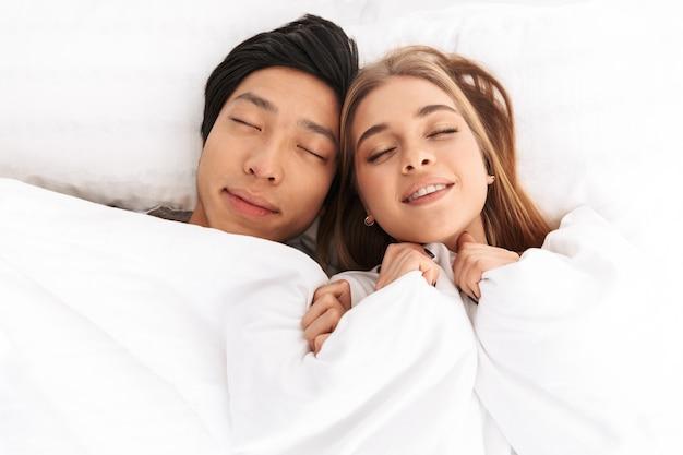 Jovem casal feliz deitado na cama de olhos fechados