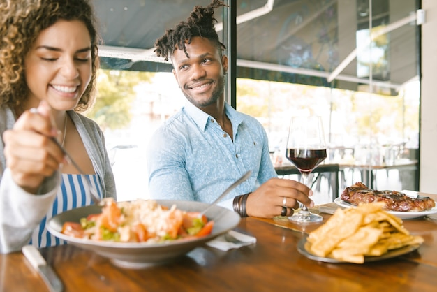 Jovem casal feliz desfrutando juntos enquanto um encontro em um restaurante.