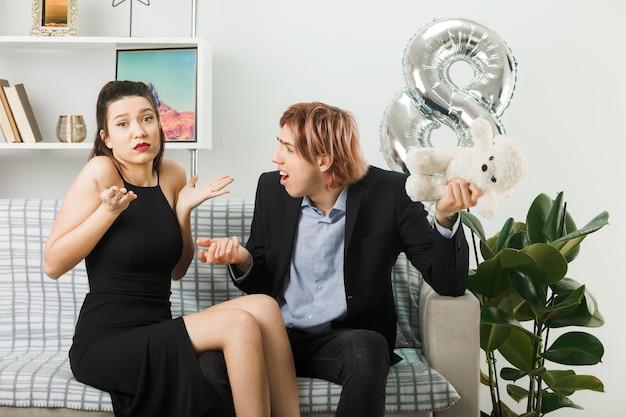 Jovem casal feliz dia da mulher com ursinho de pelúcia sentado no sofá da sala