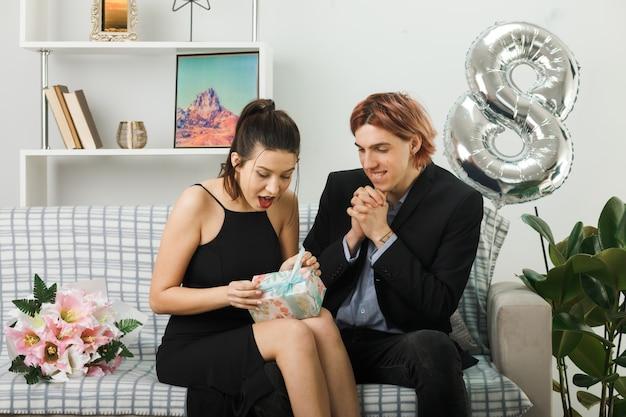 Jovem casal feliz dia da mulher segurando e olhando para o presente, sentado no sofá na sala de estar