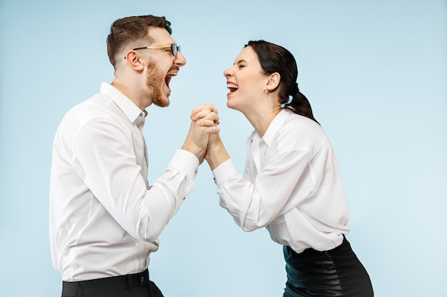 Jovem casal feliz e animado olhando para a câmera com alegria