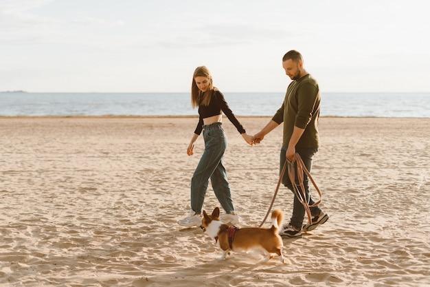 Jovem casal feliz e cachorro andando na praia. homem segurando a mão de uma mulher e um cachorrinho corgi