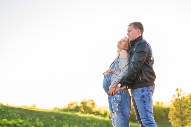 Jovem casal feliz e grávida se abraçando na natureza